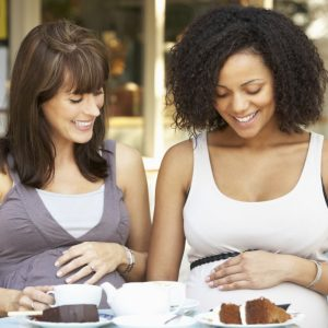 Pregnant women sitting outside café